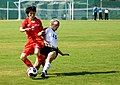 Yong Ok Jang from the Democratic Peoples Republic Korea and U.S. Army Capt. Randee Farrell fight for possession of the ball during the Military World Games' first women's soccer match in Hyderabad.JPG