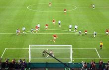 Photographie en couleurs. La photographie, prise depuis les tribunes en hauteur, représente la surface de but argentine dans laquelle l'Anglais tire le penalty face au gardien argentin qui a commencé son mouvement vers la droite alors que le ballon part sur sa gauche.