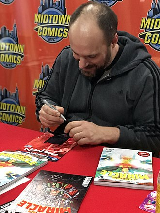 Mister Miracle - Writer Tom King autographing copies of the 2018 series and the 2019 trade paperback that collected it, during a February 15, 2019 signing at Midtown Comics in Manhattan