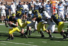 a quarterback rolls out while his offensive line blocks