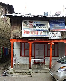 A run down a two-story building with a number of signs related to AIDS prevention