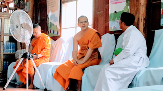 Freedom of religion in Thailand - A Buddhist monk talking to a Catholic priest in a temple in Kanchanaburi