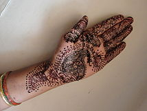 An open hand covered in artistic designs.