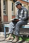 Afghan National Police Officer reading in his off time.jpg