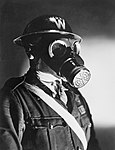 An Air Raid Warden wearing his steel helmet and duty gas mask during the Second World War. D4053.jpg