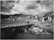 An overturned German tank lies in a shallow stream alongside a rebuilt bridge in war-ravaged Houffalizo, Belgium. - NARA - 196224