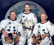 Three astronauts in white space suits. They are holding their helmets. All are light-skinned. Armstrong is smiling widely and wears his hair parted to the right. Collins has dark hair and looks the most serious. Aldrin's hair is very short. Behind them is a large photo of the Moon.