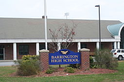 "A blue sign with gold lettering reading ""BARRINGTON HIGH SCHOOL"" stands in front of the school."