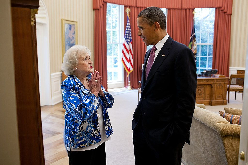Betty White standing with President Barack Obama in the Oval Office in June 2012