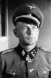 Black-and-white photo of a man wearing a peaked cap, military uniform with an Iron Cross displayed at his neck.