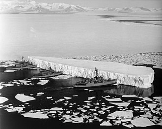 An iceberg being pushed out of a shipping lane by (L to R) USS Burton Island (AGB-1), USS Atka (AGB-3), and USS Glacier (AGB-4) near McMurdo Station, Antarctica, 1965 Burton Island, Atka, and Glacier push iceberg in McMurdo Sound (827218l).jpg