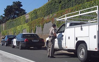 "Traffic stop - An officer of the California Highway Patrol making a traffic stop involving two other vehicles. This is sometimes called a ""double stop""."