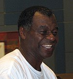 A headshot of a black man. He is looking to the right, wearing a plain white T-shirt and is smiling.