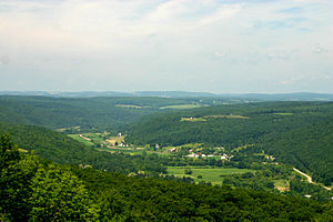 Allegheny Plateau - Canisteo River Valley from Pinnacle State Park. Glaciation in this area of the plateau removed the sharp relief that is seen in unglaciated areas of the plateau. The line of the distant peaks approximates the level of a peneplain that was uplifted to form the plateau.