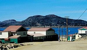Gebäude der West Baffin Eskimo Co-operative Cape Dorset, in denen Inuit-Kunstgrafik gefertigt wird; im Hintergrund: Nachbarinsel Mallikjuaq