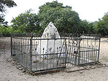 A white pyramid surrounded by a metal fence with trees in the background