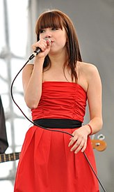 Young female singer with bangs singing into a microphone wearing a red dress.