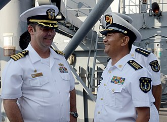 People's Liberation Army Navy - PLAN Captain Wang, commanding officer of the Chinese Type 052C destroyer 156 Jinan greets USN captain Lyle Hall during a goodwill port visit in 2015.