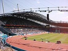 Une tribune entièrement occupée par une journée ensoleillée.  Devant elle est une piste d'athlétisme.