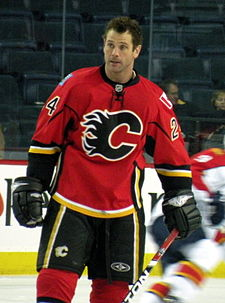 A man with short, brown hair looks to his right.  He is wearing a red uniform with black pants and a black stylized C logo on his chest.
