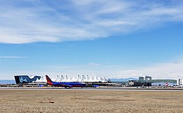 A Southwest Airlines Boeing 737-800 taxis north with the airport's Westin Hotel, Jeppesen Terminal and the skybridge to Concourse A behind.