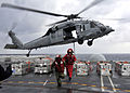 Defense.gov News Photo 101202-N-7103C-126 - U.S. Navy Airman Erik Fischer and Petty Officer 3rd Class Ryan Caballero leave a staging area as an MH-60S Sea Hawk helicopter assigned to.jpg