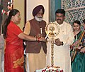 Dharmendra Pradhan and the Chief Minister of Rajasthan, Smt. Vasundhara Raje Scindia lighting the lamp at the signing ceremony of an MoU for Refinery cum Petrochemical Complex Barmer, in Jaipur, Rajasthan.jpg