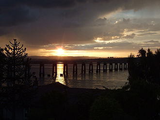 Tay Rail Bridge - At dusk. One of the stumps of the original bridge is silhouetted against the sunlit Firth.