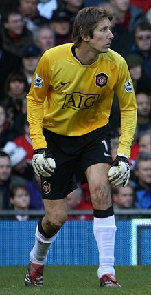 Edwin van der Sar wearing a yellow long-sleeved goalkeeper's shirt with the Manchester United FC, Nike and AIG logos printed on the front, goalkeeper gloves, black shorts with a number 1 and Nike logo on the left-leg side and Man United logo on the right-leg side, white socks, and black and red cleats.