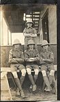 Four men in uniform sitting on planks outside one of the barracks buildings at Camp Rathbun, one of the Royal Flying Corps' pilot training camps near Deseronto. (8514093756).jpg