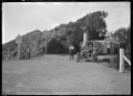 Four people with a car parked at the Summit on the Rimutaka Road, 1924 ATLIB 299529.png