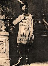 Monochrome photograph of a man standing, wearing leather books, knee-length tunic and feathered hat