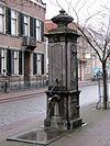 foto van Hardstenen pomp met bekroning in de vorm van een siervaas in Lodewijk XIV-vormen. Tegen het hoofdgestel en schildje met het jaartal