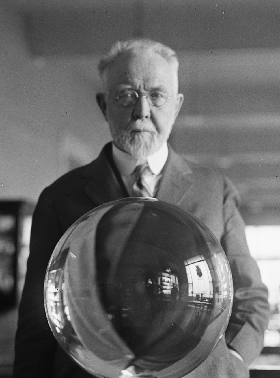 George P. Merrill, head curator of the National Museum, with the largest perfect crystal globe in the world, Washington, D.C. (cropped)