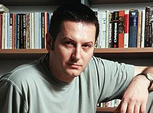 Author Georgi Gospodinov in front of a bookcase, circa 2005