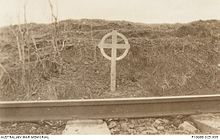 A black and white photograph of a white cross alongside a railway line