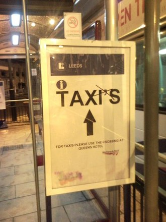 Apostrophe - A sign pointing to taxis at Leeds railway station, England, with the extraneous apostrophe crossed out by an unknown copy editor
