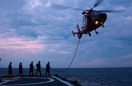 Raising a hose from Coast Guard Cutter Valiant to an HH-65 - Aerial refueling