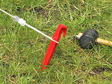 A narrower plastic tent peg in softer soil with rope and mallet. & 220px-Hering_rot.jpg