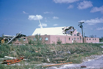 Picture of a building with severe damage to its roof, and debris strewn about in the foreground.