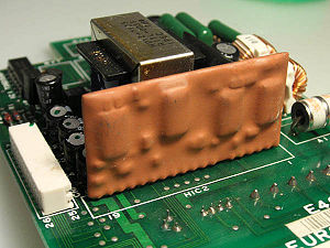 Epoxy - An epoxy encapsulated hybrid circuit on a printed circuit board.