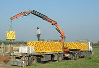 A loader crane offloading aerated concrete bricks at a building site