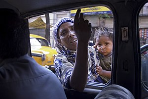 Begging - A street beggar in India gets into the car