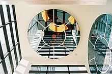 Two circular mirrors with circle and wagon spoke designs are set into an ivory colored ceiling and wall. They reflect windows in black rectangular frames in two other walls.