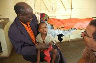 Peter Agre - A Zambian villager holding his grandson whose life was saved by Dr. Philip Thuma. Afflicted with cerebral malaria, the child was near death but was left with permanent blindness.