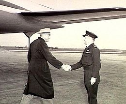 Three-quarter shot of two men at airport shaking hands, one in civilian clothes with dark overcoat and light-coloured hat, the other in military uniform with peaked cap and pilot's wings on battle jacket. An aircraft's tail plane is above and behind the two men.