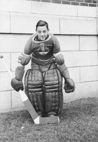 A teenage Plante assumes the traditional goaltender stance, slightly crouched with legs together, wearing goaltender pads on his legs, his team sweater, and holding a goaltender stick in his right hand with the blade of the stick in front of his feet