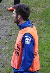 White man with dark hair and beard, wearing sports kit outdoors