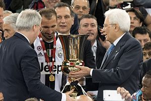 Giorgio Chiellini - Chiellini (center), Juventus' captain during the 2016 Coppa Italia Final, receives the trophy by the President of the Italian Republic Sergio Mattarella (right).