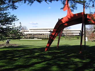 """Donald M. Kendall Sculpture Gardens - South end of the gardens looking north at PepsiCo world headquarters, past the expanse of the south lawn. Shown are part of Alexander Calder's red """"Hats Off"""" and, in the distance, David Wynne's """"Grizzly Bear"""" (at left). Two other works can be seen in the distance."""